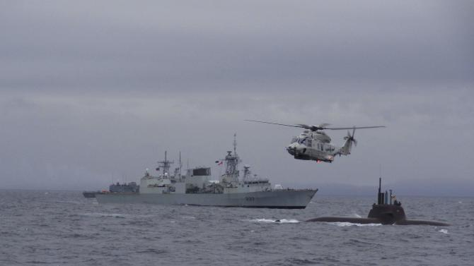 A Canadian warship and a German submarine participate in NATO's Dynamic Mongoose anti-submarine exercise in the North Sea off the coast of Norway
