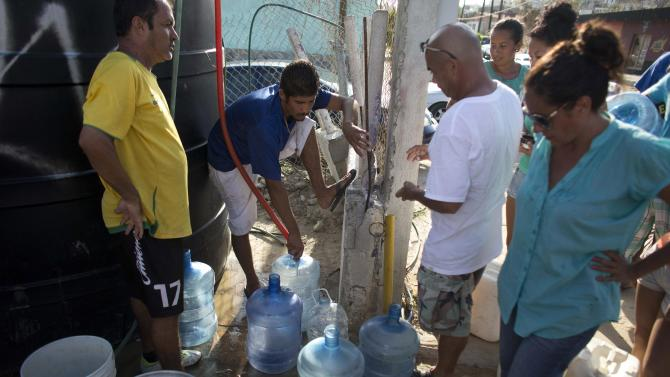 People fill bottles at a water station in San Jose de los Cabos, Mexico, Wednesday, Sept. 17, 2014. Federal Electricity Commission officials said Thursday, some 2,500 power poles were toppled by Hurricane Odile, which struck on Sunday as a Category 3 storm. Water and electricity service remained out and phone service was intermittent Thursday. (AP Photo/Dario Lopez-Mills)
