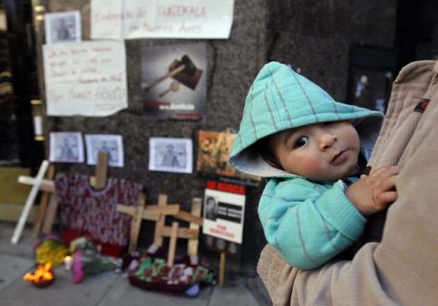 A baby looks on in front of a shrine for victims killed by the armed forces in Guatemala during a demonstration outside Guatemala's Embassy in Buenos Aires