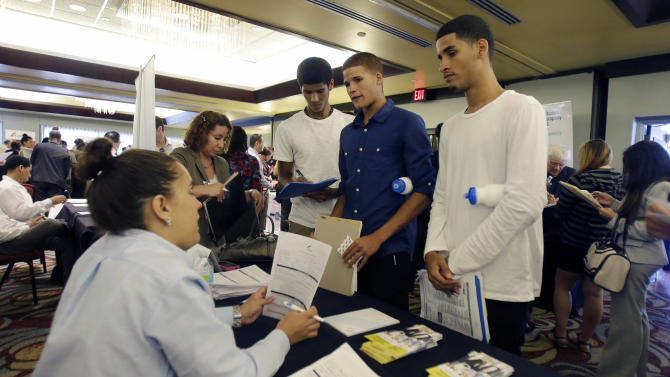In this Wednesday, Aug., 14, 2013, photo, job seekers Emilio Ferrer, Brian ferrer, center, and Jonathan, right, of Hollywood, Fla., talk to a FirstService representative at a job fair in Miami Lakes, Fla. The Labor Department reports on the number of Americans who applied for unemployment benefits for third week of August on Thursday, Aug. 29, 2013. (AP Photo/Alan Diaz)