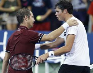 Milos Raonic of Canada congratulates Richard Gasquet of France after Gasquet's win at the U.S. Open tennis championships in New York