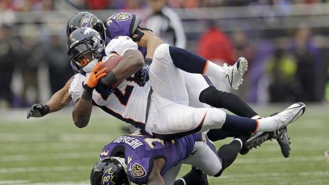 Denver Broncos running back Knowshon Moreno is stopped by Baltimore Ravens inside linebacker Brendon Ayanbadejo, top, and defensive back James Ihedigbo, bottom during the first half of an NFL football game in Baltimore, Sunday, Dec. 16, 2012. (AP Photo/Patrick Semansky)