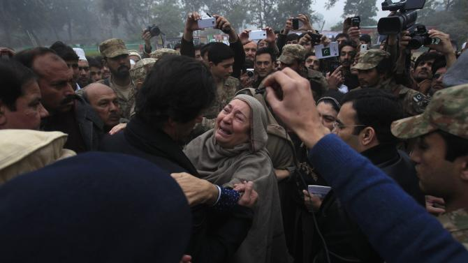Grandmother of Muhammad Ali Khan, a student who was killed during an attack by Taliban gunmen on Army Public School, reacts during a visit by Khan, chairman of Pakistan Tehrik-e-Insaf political party, at the school in Peshawa