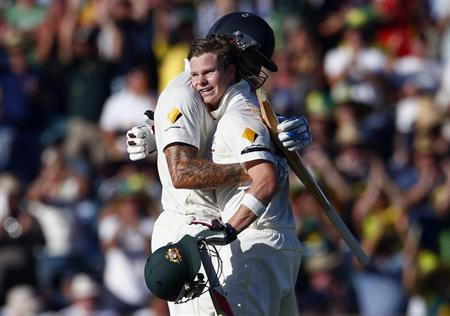 Australia's Steve Smith (R) hugs team mate Mitchell Johnson after reaching his century during the first day of the third Ashes cricket test against England at the WACA ground in Perth December 13,