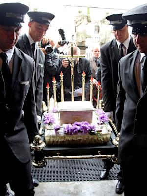 """Soldiers in ceremonial uniform carry the metal urn of Poland's celebrated dissident writer Slawomir Mrozek into St. Peter and Paul church in Krakow, Poland on Tuesday, Sept. 17, 2013 during his state burial. Mrozek died Aug. 15 in Nice, France, aged 83. He made his name across the world with surrealist plays, notably the 1964 """"Tango,"""" which slyly ridiculed communism. (AP Photo/Tomasz Jagodzinski) POLAND OUT"""