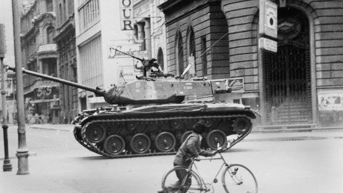 FILE - In this Sept. 11, 1973 file photo, a boy pushes a bicycle across a deserted street as an army tank moves towards La Moneda presidential palace during a coup against President Salvador Allende's government, after which Gen. Augusto Pinochet seized power, in Santiago, Chile. On Wednesday, Sept. 11, 2013, Chile marks the 40th anniversary of the coup. (AP Photo/File)