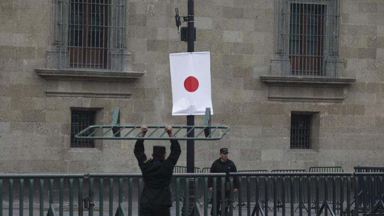 Security personnel secure the perimeter around the presidential palace near a Japanese flag before a visit by Japan's Prime Minister Shinzo Abe in Mexico City