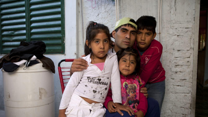 "Cristian Marcelo Reynoso, center, poses inside his home with his children, Milagro, 5, left, Oriana, 3, bottom, and Nahuel, 10, right, in their home in the Villa 21-24 slum in Buenos Aires, Argentina, Thursday, March 14, 2013.  At Villa 21-24, a slum so dangerous that most outsiders wouldn't dare go in, Jorge Mario Bergoglio often showed up unannounced to share laughs and sips of mate, the traditional Argentine herbal tea. Reynoso, 27, said their favorite soccer club, San Lorenzo, ""was going through a bad streak the last time they talked, and he told me that even if it was losing you couldn't desert it ... It's like people. We all hit the bottom of the well, but you can always be rescued from the bottom."" Reynoso is trying to kick off an addiction to crack cocaine through the local church's rehab program. (AP Photo/Victor R. Caivano)"