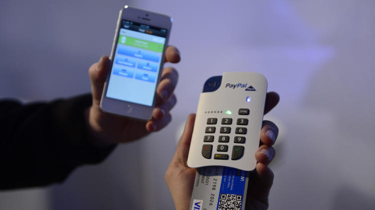 "FILE - In this Feb. 27, 2013 file photo, a man uses the ""Paypal here"" system of payment with the phone at the Mobile World Congress, the world's largest mobile phone trade show, in Barcelona, Spain. (AP Photo/Manu Fernandez, File)"