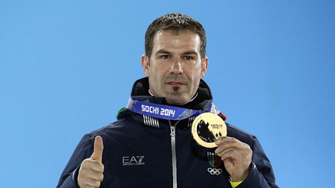 Men's luge singles bronze medalist Armin Zoeggeler of Italy gestures while holding his medal during the medals ceremony at the 2014 Winter Olympics, Monday, Feb. 10, 2014, in Sochi, Russia
