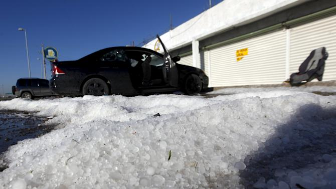 Vehicles are seen parked on a street near hailstones after a hail storm in Ciudad Juarez, Mexico