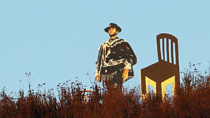 A life-sized cardboard cutout of actor Clint Eastwood next to an empty chair is seen overlooking a freeway in Glendale, Calif., Tuesday, Sept. 4, 2012. The chair is a reference to Eastwood's 12-minute speech during last week's Republican National Convention that drew both criticism and praise for Eastwood. Life-sized cardboard cutouts of Eastwood, John Wayne and Gene Autry have been keeping watch over Glendale for months as part of an effort by Los Angeles resident Justin Stadel to spur a conversation about public art. (AP Photo/Reed Saxon)