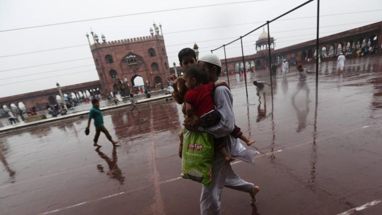 A Muslim man carries his children after offering evening prayers, as it rains on the last day of the holy fasting month of Ramadan in India, at the Jama Masjid in the old quarters of Delhi