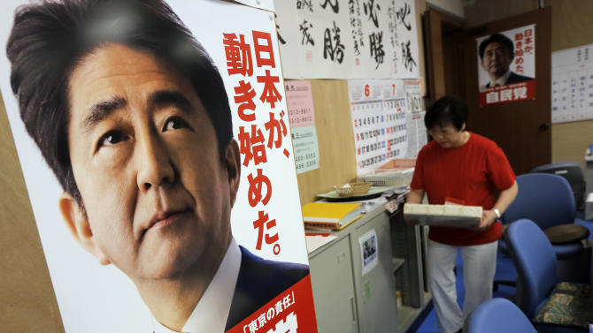 """A poster of Japanese Prime Minister Shinzo Abe is displayed at the ruling Liberal Democratic Party headquarters in Tokyo, Friday, June 14, 2013. Japan's Cabinet approved a blueprint for reforms Friday meant to improve competitiveness and shore up long-term growth in the world's third-largest economy as its population ages and shrinks. Abe has outlined the reforms in whole and in part since taking office in December, calling them the """"third arrow"""" in his economic recovery program. The poster reads: """"Japan has begun to move."""" (AP Photo/Itsuo Inouye)"""