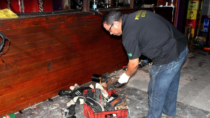 In this photo released by Policia Civil do Rio Grande do Sul, a police officer inspects victims' belongings after a fire at the Kiss nightclub in Santa Maria City, Rio Grande do Sul state, Brazil, Tuesday, Jan. 29, 2012. The blaze began at around 2:30 am local time on Sunday, during a performance by Gurizada Fandangueira, a country music band that had made the use of pyrotechnics a trademark of their shows. (AP Photo/Policia Civil do Rio Grande do Sul)