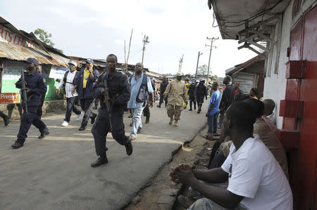 Liberian security forces patrol a street after clashes at West Point neighbourhood in Monrovia