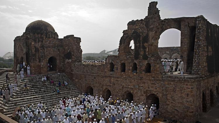 Indian Muslims take part in Eid al-Fitr prayers in the ruins of the Feroz Shah Kotla Mosque in New Delhi, Tuesday, July 29, 2014. Millions of Muslims across the world are celebrating the Eid al-Fitr holiday, which marks the end of the month-long fast of Ramadan. (AP Photo/Bernat Armangue)
