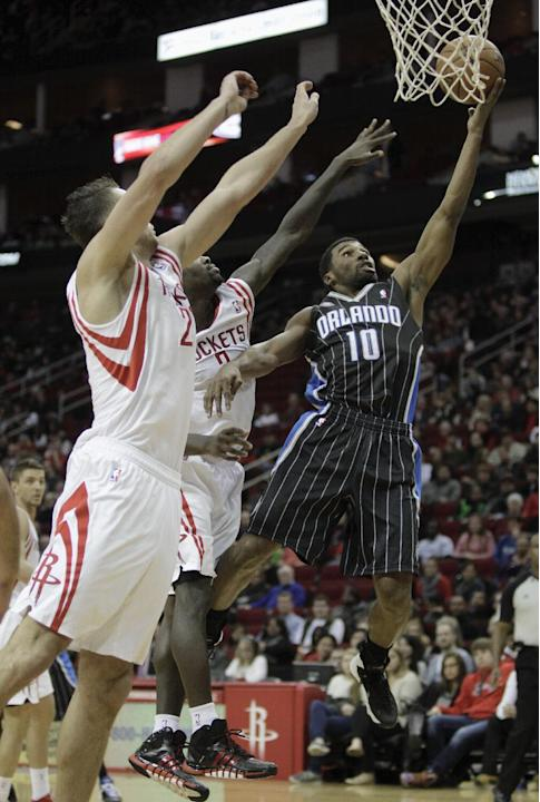 Orlando Magic point guard Ronnie Price (10) drives to the basket around Houston Rockets point guard Aaron Brooks, center, and power forward Donatas Motiejunas, left, during the first quarter of an NBA