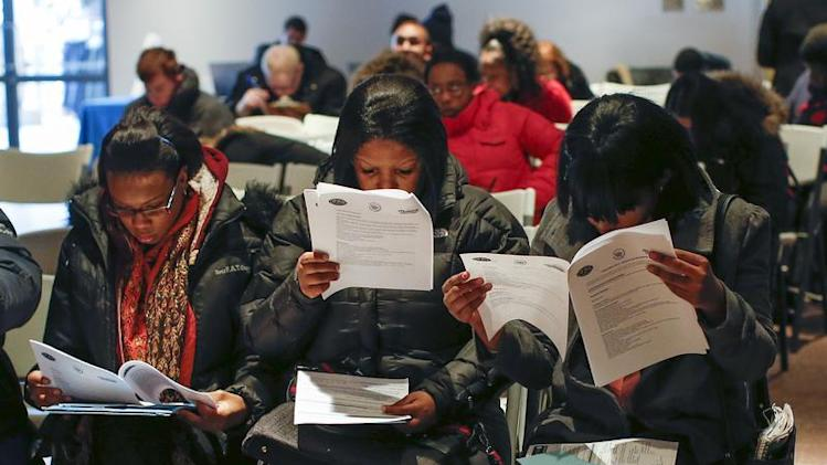 People fill out application forms before a screening session for seasonal jobs at Coney Island in the Brooklyn borough of New York