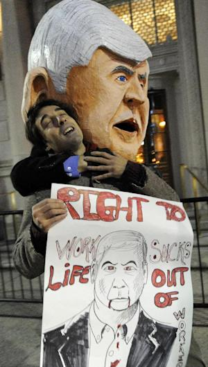 A protester, Bruce Fealk,  dressed like Governor Rick Snyder, holds Vassilis Jacobs during a demonstration at the Detroit Athletic Club in Detroit on Thursday, March 28, 2013.  Unionized workers and others plan to protest outside the Detroit Athletic Club as Snyder will address a 'Pancakes & Politics' breakfast. The protesters are demonstrating against the right-to-work law that takes effect Thursday that allows workers to decide not to pay dues to a union as a condition of employment.  (AP Photo/Detroit News, David Coates)  DETROIT FREE PRESS OUT; HUFFINGTON POST OUT