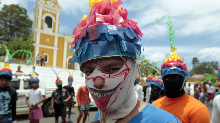A masked man takes part in a Good Friday procession during Holy Week celebrations in Masatepe