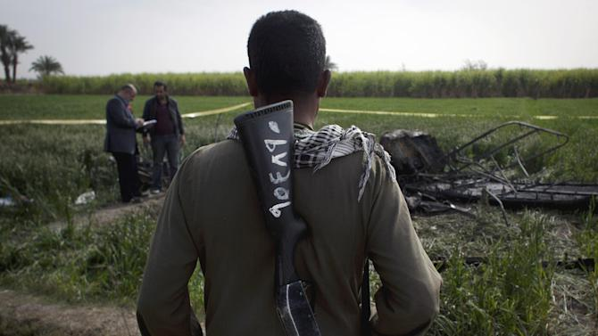 An Egyptian field guard looks at two inspectors of the Civil Aviation Authority working at the site of the balloon accident, in Luxor, Egypt, Tuesday, Feb. 26, 2013. A hot air balloon flying over Egypt's ancient city of Luxor caught fire and crashed into a sugar cane field on Tuesday, killing at least 19 foreign tourists in one of the world's deadliest ballooning accidents and handing a new blow to Egypt's ailing tourism industry. (AP Photo/Nasser Nasser)
