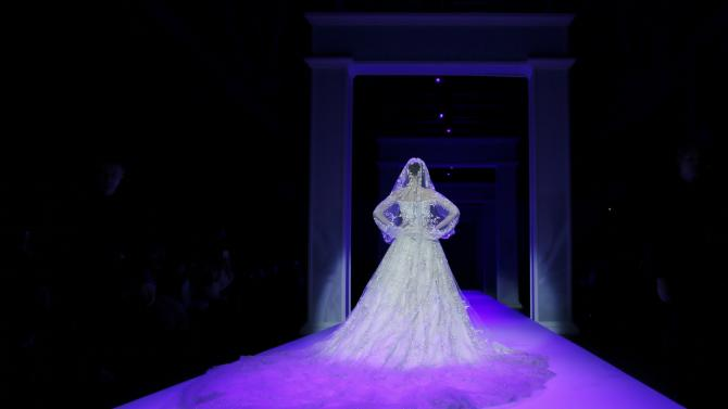 A model presents a creation by Australian designers Tamara Ralph and Michael Russo as part of their Haute Couture Spring Summer 2015 fashion show for British fashion house Ralph & Russo in Paris