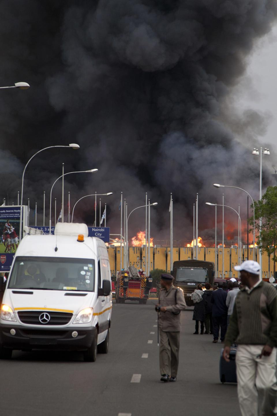 A policeman stands guard as a fire engulfs the International arrivals hall at the Jomo Kenyatta International Airport in Nairobi, Kenya Wednesday, Aug. 7, 2013. The Kenya Airports Authority said the Kenya's main international airport has been closed until further notice so that emergency teams can battle the fire. (AP Photo/Sayyid Azim)