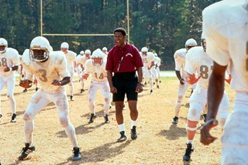 Academy Award? winner Denzel Washington (center) stars as high school football coach Herman Boone who, in 1971, is caught in the middle of integrating an all-black and all-white football team and face