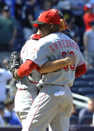 Cincinnati Reds catcher Devin Mesoraco, left, hugs relief pitcher Jose Arredondo (33) after the Reds defeated the New York Yankees 6-5 in an interleague baseball game on Saturday, May 19, 2012, at Yankee Stadium in New York. (AP Photo/Kathy Kmonicek)