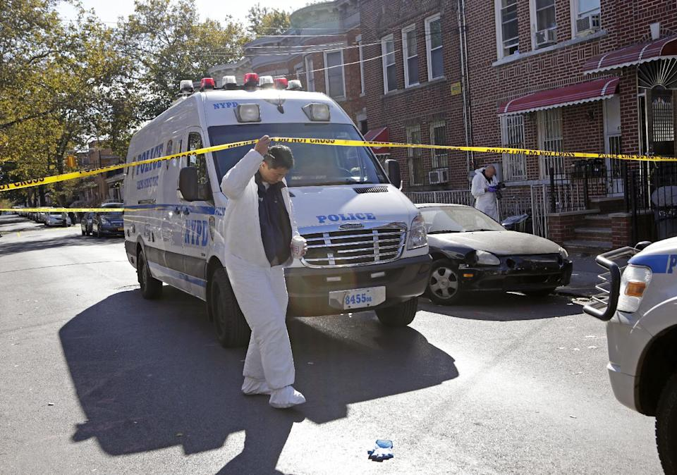 Crime scene specialists work at the scene of a fatal stabbing, Sunday, Oct. 27, 2013, in the Brooklyn borough of New York. Police say a mother and her four young children were killed in a late night stabbing rampage at the Sunset Park, Brooklyn home, far right. (AP Photo/Kathy Willens)