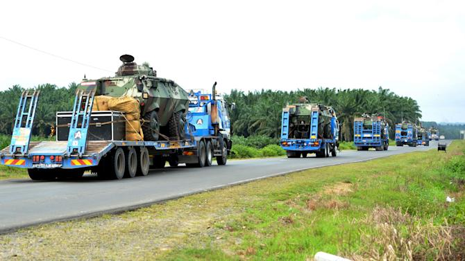 Armed personnel carriers are transported to the area where the stand-off between Filipino gunmen and Malaysian police took place in Tanduo village, Sabah state's Lahad Datu, Malaysia Monday, March 4, 2013. Malaysia sent hundreds of soldiers to a Borneo state Monday to help neutralize armed Filipino intruders who have killed eight police officers in the country's bloodiest security emergency in years. Nineteen Filipino gunmen have also been slain since Friday in skirmishes that shocked Malaysians unaccustomed to such violence in their country, which borders insurgency-plagued southern provinces in the Philippines and Thailand. (AP Photo/Bernama News Agency) MALAYSIA OUT, NO SALES, NO ARCHIVE