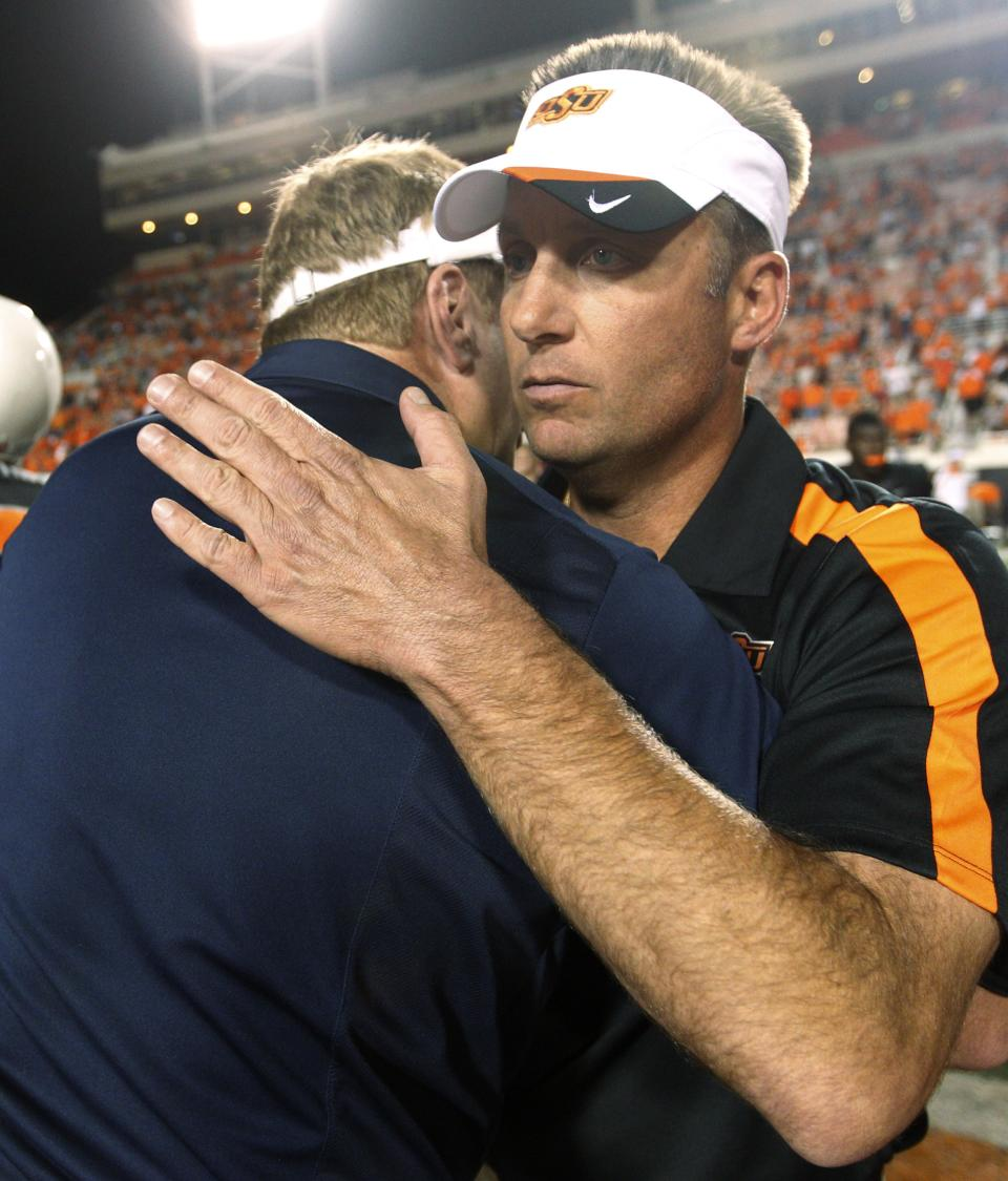 Oklahoma State head coach Mike Gundy, right, greets Arizona head coach Mike Stoops, left, following their NCAA college football game in Stillwater, Okla., Thursday, Sept. 8, 2011. Oklahoma State won 37-14. (AP Photo/Sue Ogrocki)