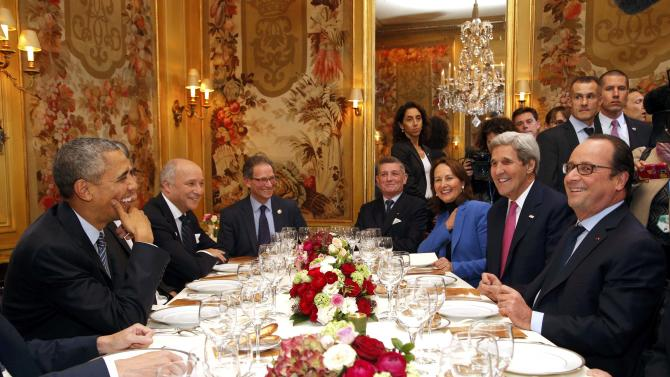 US President Barack Obama sits with French President Francois Hollande during a dinner at the Ambroisie restaurant in Paris