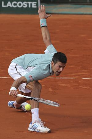 Serbia's Novak Djokovic returns against Germany's Tommy Haas defeating him in three sets 6-3, 7-6, 7-5, in their quarterfinal match at the French Open tennis tournament, at Roland Garros stadium in Paris, Wednesday June 5, 2013. (AP Photo/Michel Euler)