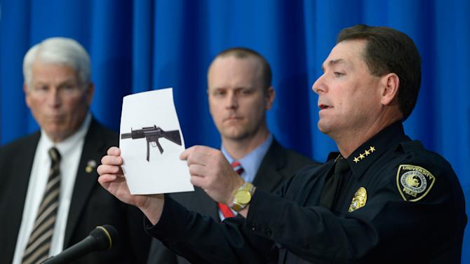 University of Central Florida police Chief Richard Beary, right, shows an example of the assault rifle, along with explosive devices, found in the dorm room of James Oliver Seevakumaran, who died of an apparent suicide in the room, Monday, March 18, 2013, in Orlando, Fla. Watching are UCF president John Hitt, left, and Grant Heston, UCF associate vice-president of communications and public affairs. (AP Photo/Phelan M. Ebenhack)