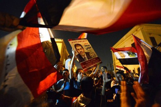Egyptians celebrate the victory of the Muslim Brotherhood's candidate, Mohamed Morsi (portrait), in Egypt's presidential elections in Cairo's Tahrir Square on June 24, 2012. Morsi became the first Islamist to be elected president of the Arab world's most populous nation and after a divisive election battle pledged to be a leader for all Egyptians