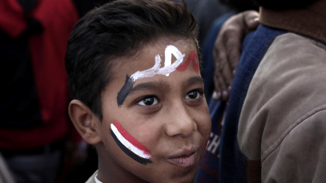 """A boy with the colors of the Egyptian flag and Arabic that reads, """"Egypt,"""" painted on his face attends a demonstration in Tahrir Square, Cairo, Egypt, Friday, Nov. 30, 2012. Liberal and secular parties held major protests against Egyptian President Mohammed Morsi's latest decrees granting himself almost complete powers. (AP Photo/Nariman El-Mofty)"""