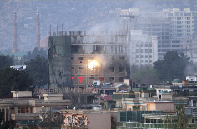Gunfire and smoke is seen coming out of a building occupied by militants during a battle with Afghan-led forces, in Kabul, Afghanistan, Monday, April 16, 2012. The Afghan capital awoke Monday to a sec