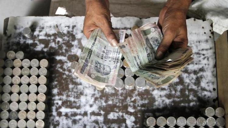 A man exchanging damaged currency counts 100 rupee notes along a roadside in Kolkata August 30, 2013. REUTERS/Rupak De Chowdhuri/Files