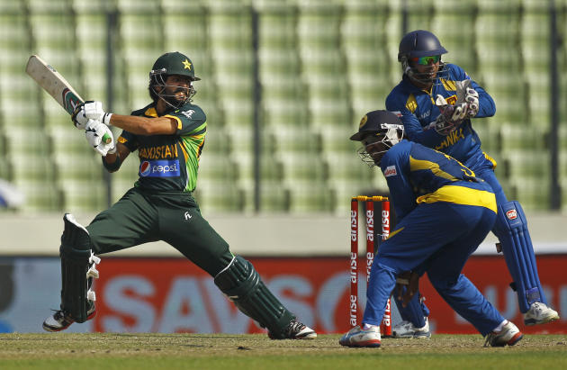Pakistan's Fawad Alam, left, plays a shot in front of Sri Lankan wicketkeeper Kumar Sangakkara, right, and a teammate during their Asia Cup final cricket match in Dhaka, Bangladesh, Saturday, March 8,