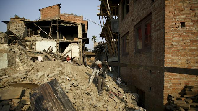 A man carrying a block of wood recovered from his house walks along debris of collapsed houses, a month after the April 25 earthquake in Kathmandu