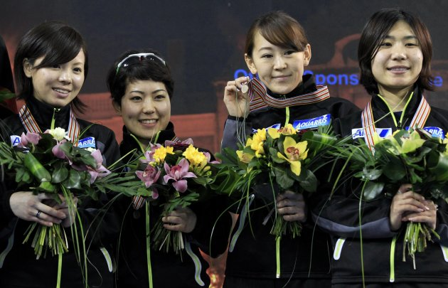 Third placed Japan's team celebrate on the podium after the women's 3000m relay final at the ISU World Short Track Speed Skating Championships in Debrecen