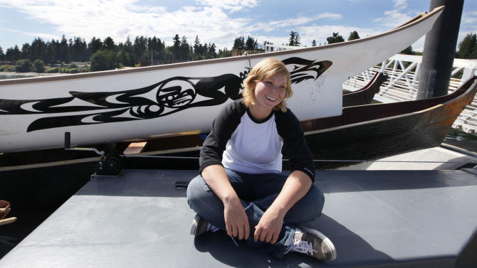 Heather Purser, a Suquamish tribal member who worked to change the tribes marriage ordinance to include same-sex couples, sits next to tribal canoes on the reservation Tuesday, Aug. 2, 2011, in Suquamish, Wash. The change in tribal law came after a four-year campaign by Purser, 28, to get the American Indian Tribe in Washington state to adopt a law recognizing gay marriage. The Suquamish Tribal Council voted Monday, Aug. 1, to extend marriage rights to same-sex couples on its reservation near Seattle, making it only the second tribe in the country known to do so. (AP Photo/Elaine Thompson)