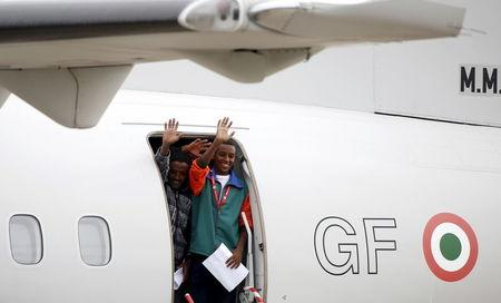 Migrants wave as they board a plane before being relocated to Sweden at Ciampino military airbase in Rome