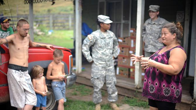 Dewan Dunbar, right, discusses living without power after members of the West Virginia National Guard delivered food and water to her home Thursday, July 5, 2012 in Heaters, W.Va. Residents in the Heaters area have been without power since Friday, June 29, 2012 following a severe storm. (AP Photo/Jeff Gentner)
