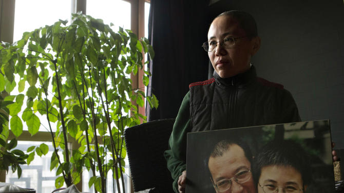 Liu Xia, wife of 2010 Nobel Peace Prize winner Liu Xiaobo, poses with a photo of her and her husband during her first interview in more than two years at her home in Beijing, China, on Thursday, Dec. 6, 2012. Liu trembled uncontrollably and cried Thursday as she described how her confinement under house arrest has been absurd and emotionally draining in the two years since her jailed activist husband was named a Nobel Peace laureate.  (AP Photo/Ng Han Guan)
