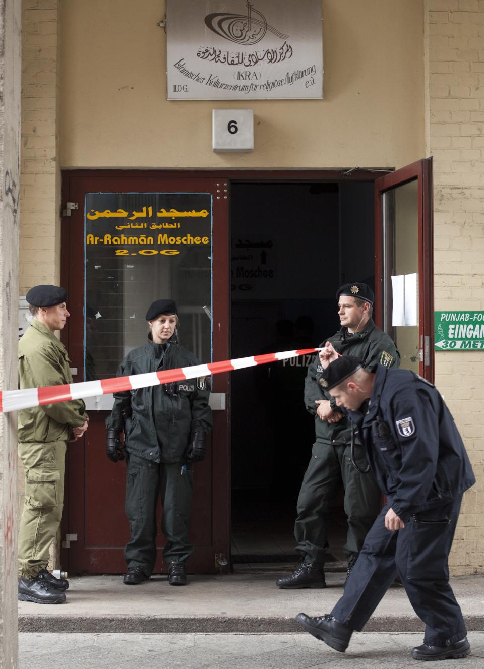 German police officers guard the entrance of an Islamic cultural center as they search it in Berlin, Thursday, Sept. 8, 2011. German police on Thursday detained two men suspected of obtaining potential ingredients for a bomb and searched an Islamic center where the pair had spent time. (AP Photo/Markus Schreiber)