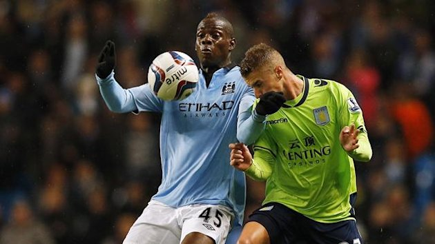 Manchester City&#39;s Mario Balotelli (L) challenges Aston Villa&#39;s Joe Bennett during their English League Cup soccer match at The Etihad Stadium in Manchester, northern England, September 25, 2012
