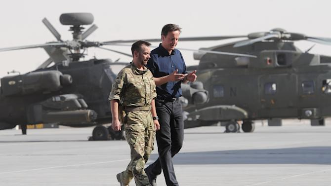 Britain's Prime Minister, David Cameron, walks along the helicopter flight line accompanied by an unidentified officer as he arrives at Camp Bastion in Helmand Province, Afghanistan, Wednesday, July 18, 2012 during a surprise trip to the area. Earlier he met Afghan National Police chiefs. (AP Photo/Stefan Rousseau, Pool)